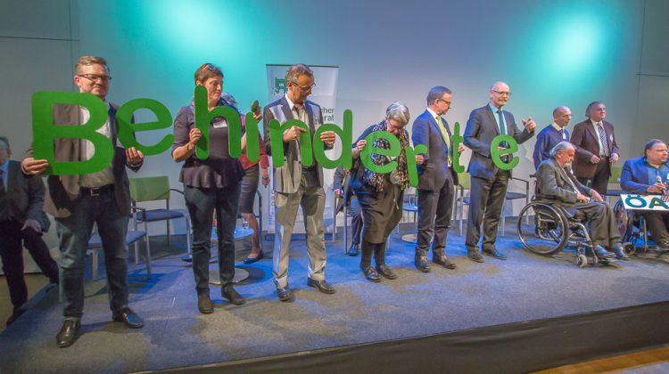 Die Delegierten auf der Bühne halten Buchstaben mit dem neuen Namen Behindertenrat