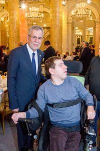 Bundespräsident und ein Gast im Rollstuhl
