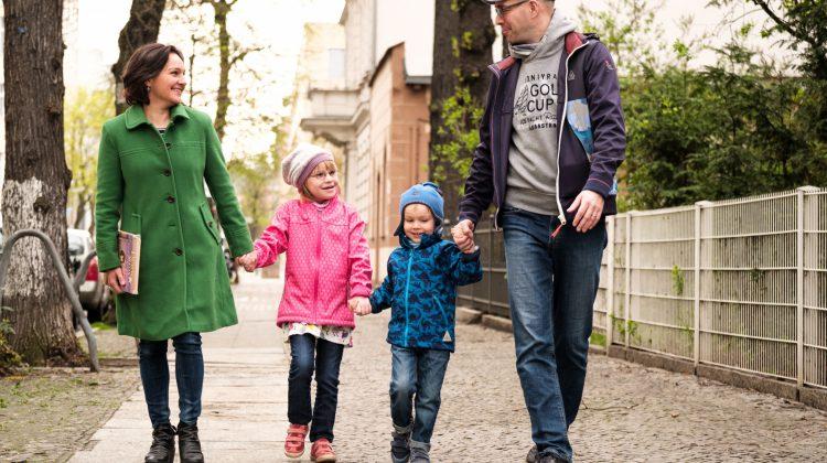 Frau, Mädchen, Junge, Mann, halten sich an den Händen, gehen auf einer Straße