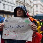 """Mann auf einer Straße hält Schild mit """"Mehr Gerechtigkeit für Alle"""""""