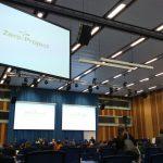 Großer Veranstaltungsraum, Bühne, Drei große Screens, auf einem steht Zero Project Conference