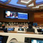 Saal der Sitzung mit dem UN Komitee, Tisch emit Bildschirmen, Bühne mit Bildschirm dahinter