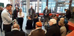 Im Bahnhofs-Voyer sitzt eine Gruppe von Menschen mit und ohne Behinderungen