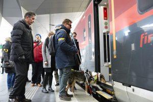 Ein Mann, der einen Langstock nutzt, sowie einen Führhund an seiner Seite hat steht vor einer offenen Zugtür
