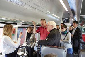 Ein Gruppe von Menschen mit nd ohne Behinderungen blickt im Zuginneren auf den oberen Rand der Fenster und ist im Gespräch