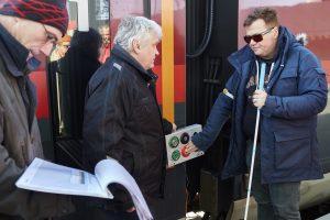 Vor einem Zug stehen drei Männer, eine Person mit Langstock drückt auf die Öffnungstaste eine Person blickt auf ein Klappbrett