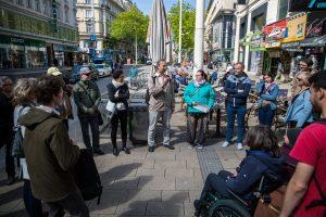 Emil Benesch spricht, 25 Personen mit und ohne Behinderungen stehen im Halbkreis auf Mariahilfer Straße