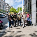 Teilnehmer*innen mit und ohne Behinderugnen in Bewegung auf einem Gehsteig