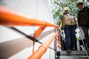 Mann mit Blindenschleife testet einen Handlauf eines U-Bahn Abganges