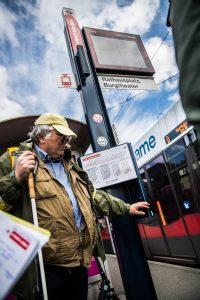 Straßenbahnstation, man mit Langstock erstastet scharfe Kante eines Informationskastens