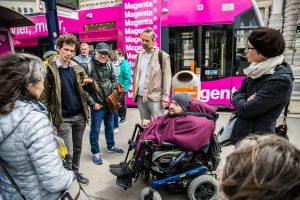 Teilnehmergruppe mit und ohne Behinderungen bei der Straßenbahnstation
