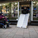 Mann breitet Rampe vor einem Geschäft aus, daneben steht ein Rollstuhlfahrer