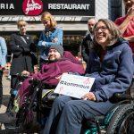 """Maria Grundner in einem Rollstuhl sitzend und lächelnd hält eine Tafel mit der Aufschtift """"Komm raus"""""""