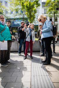 Vera Layr steht an einer Abzweigung des Blindenleitsystems in der Mariahhilfer Strasse und spricht zu blinden Menschen.