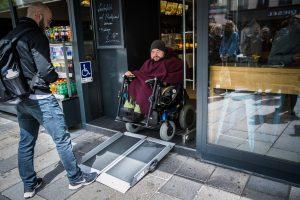 E-Rollstulnutzer ist dabei ein Geschäft über eine mobile Rampe zu verlassen.