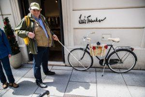 Bliunder Mensch mit Langstock trifft auf Fahrrad, abgestellt an der Hausmauer