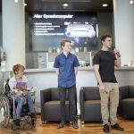 2 HTL Schüler und Natascha Toman im Rollstuhl bei der Präsentation. Im Hintergrund ist eine PPP zu sehen.