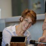 Natascha Toman lächelt, im Vordergrund am Rollstuhl montiert ihr neuer Sprachcomputer