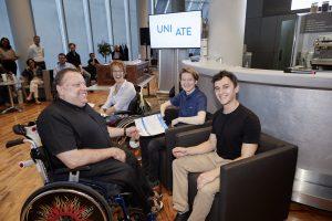 Herbert Pichler, im Rollstuhl übergibt Urkunden an das sitzende Team um Natascha Toman