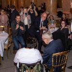 Van der Bellen gemeinsam mit einer Rollstuhlnutzerin im Blitzlichtgewitter mehrer Kameras