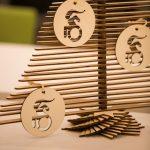 Auf dem Weihnachtsbaum aus dünnen Holzblättern hängen drei runde Anhänger aus Holz mit sportlichen RollstuhlfahrerInnen.
