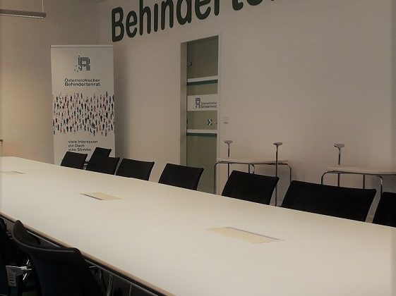 Besprechungsraum des Behindertenrat. Weißer Tisch, Grüne Sessel, Schriftzug über der Tür mit 'Behindertenrat'