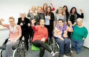 15 Frauen mit und ohne Behinderugnen sind in Kampfpose und blicken in die Kamera
