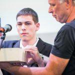 Schüler auf der Bühne hält einen Stift und tippt auf Elemente in einer Art Holzschublade, gehalten von einem Mann
