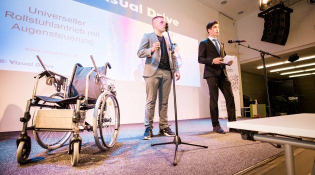 2 Schüler stehen auf der Bühne und präsentieren. Neben ihnen ihr Prototyp, ein adaptierter Rollstuhl.