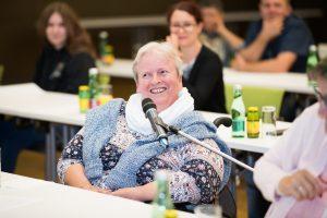 Frau aus dem Publikum mit Mikrofon an einer Stange
