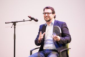 Mann mit Brille sitzend auf der Bühne, hält ein Dreiecksförmiges Gerät