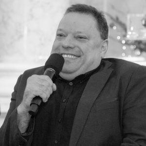 Portrait von Herbert Pichler in Schwarz Weiß, er lächelt und hält ein Mikrofon
