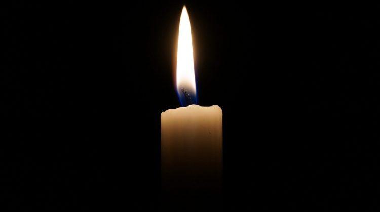 brennende Kerze vor schwarzem Hintergrund