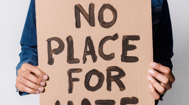 Person hält ein Schild: No pLace for Hate