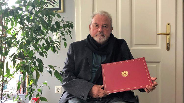 Dr. Voget hält eine schmuckvolle Mappe mit österreichischem Wappen darauf