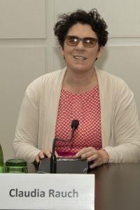 Claudia Rauch sitzt am Podium, ihre Hände liegen auf einer Braille-Zeile