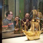 Im Vordergrund sieht man ein goldenes kleines Schiff in einem Glaskasten, dahinter eine Personengruppe die dem Schiff zugewandt ist