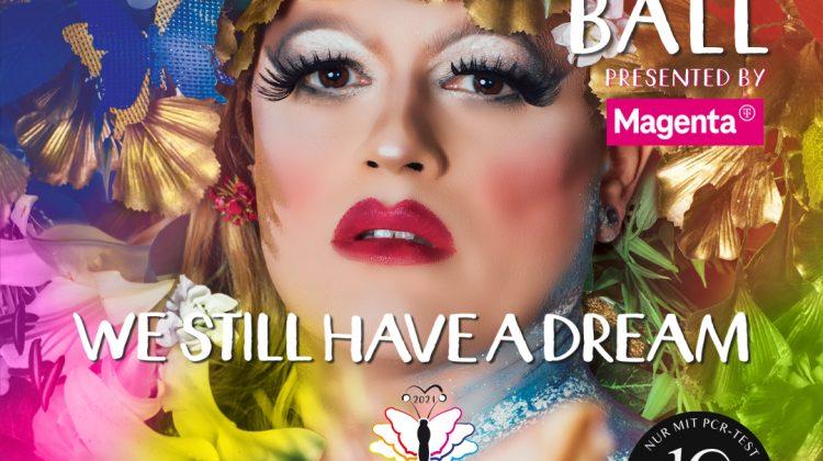 Eine stark geschminkte Person, als Frau gelesen, umgeben von bunten Farben. 13. Diversity Ball - We still have a dream